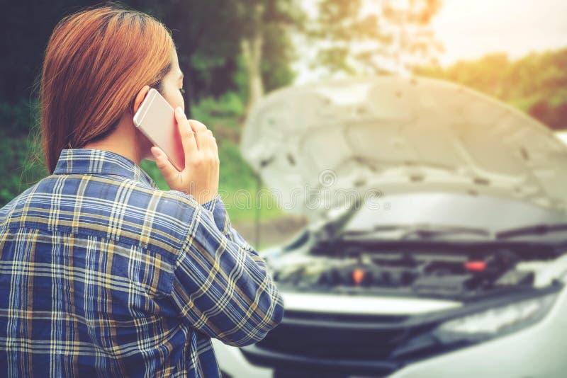 Jovem mulher que chama para o auxílio com seu carro dividido por t fotografia de stock royalty free