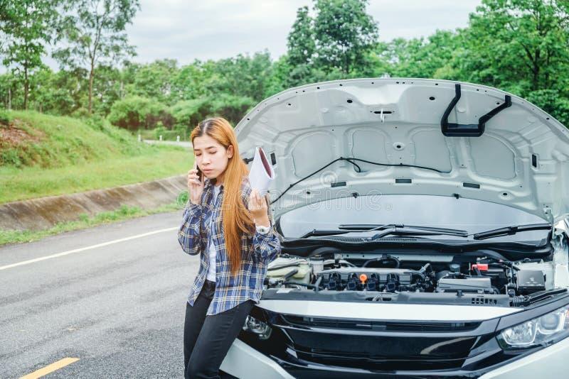 Jovem mulher que chama para o auxílio com seu carro dividido por t imagem de stock