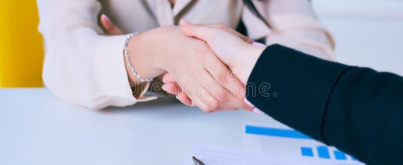 Jovem mulher que chega para uma entrevista de trabalho Executivos do aperto de mão no escritório moderno fotos de stock