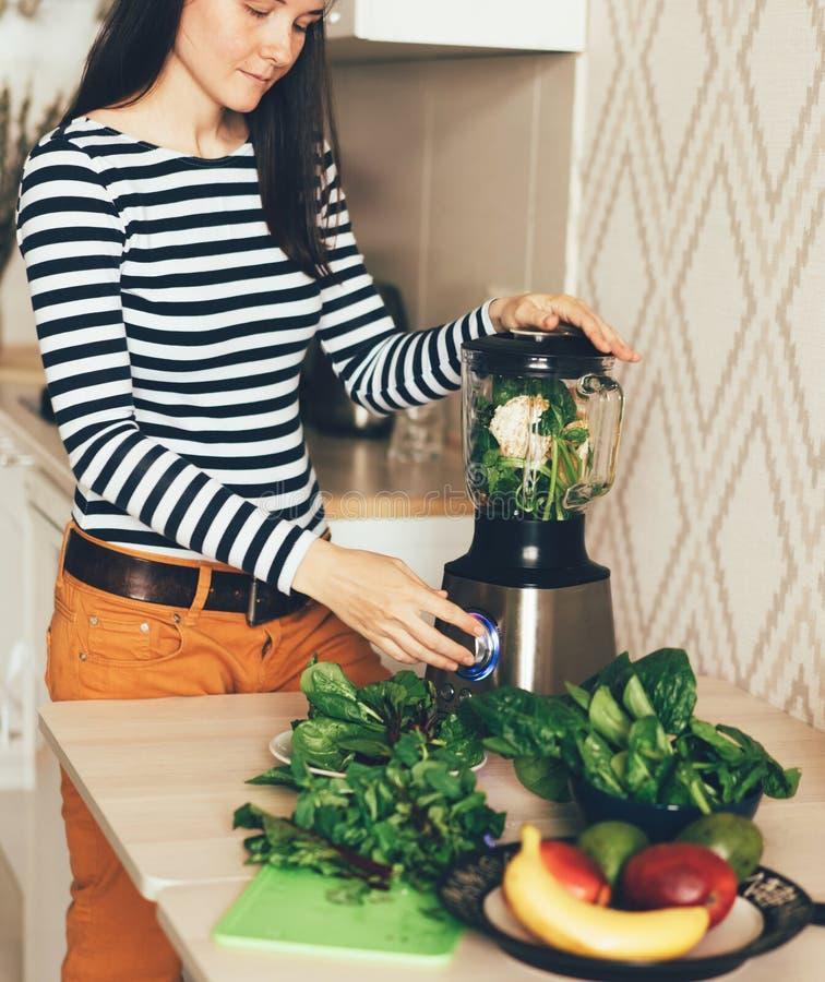 Jovem mulher que chicoteia vegetais e folhas em um misturador foto de stock