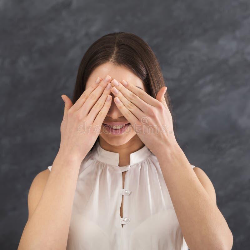 A jovem mulher que cobre os olhos com as mãos, não vê nenhum mal foto de stock