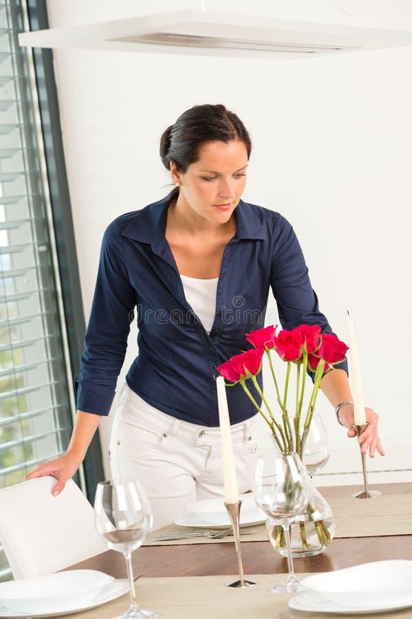 Jovem mulher que coloca as rosas da tabela da vela românticas imagem de stock royalty free