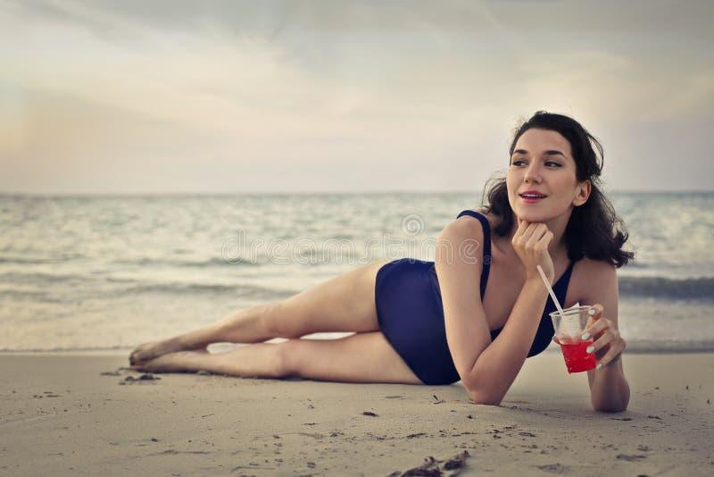 Jovem mulher que coloca na praia fotos de stock royalty free