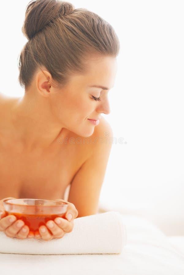 Jovem mulher que coloca na tabela da massagem com placa do mel imagens de stock royalty free