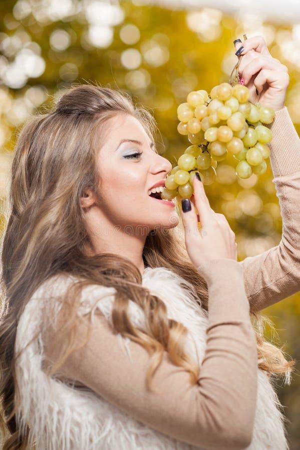 Jovem mulher que come as uvas exteriores Fêmea loura sensual que sorri guardando um grupo de uvas verdes Menina justa bonita do c imagem de stock