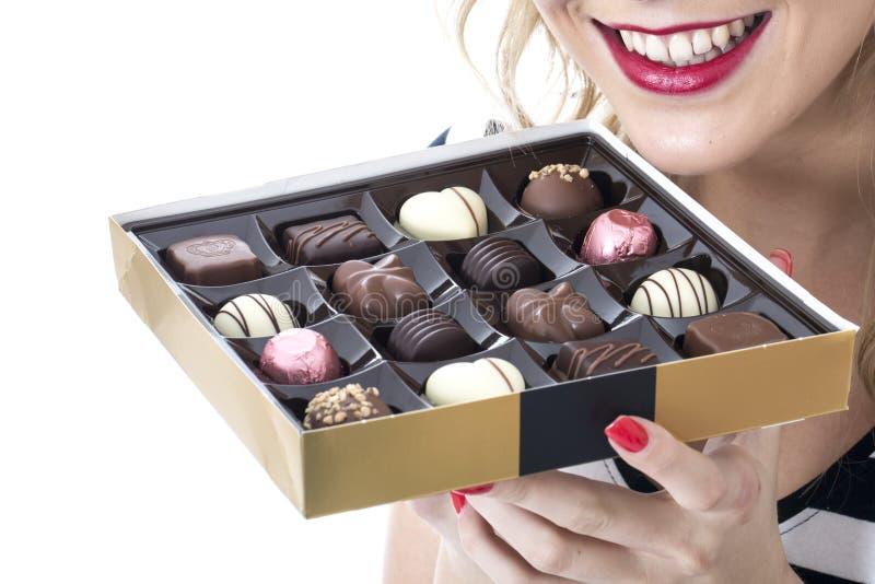 Jovem mulher que come a caixa dos chocolates imagem de stock