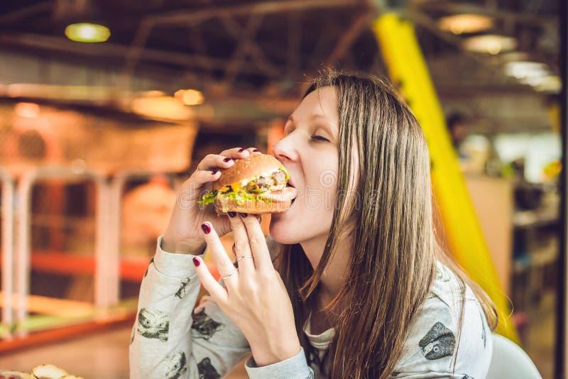 Jovem mulher que come a mulher do Hamburger que come a comida lixo, Hamburger do alimento gordo foto de stock