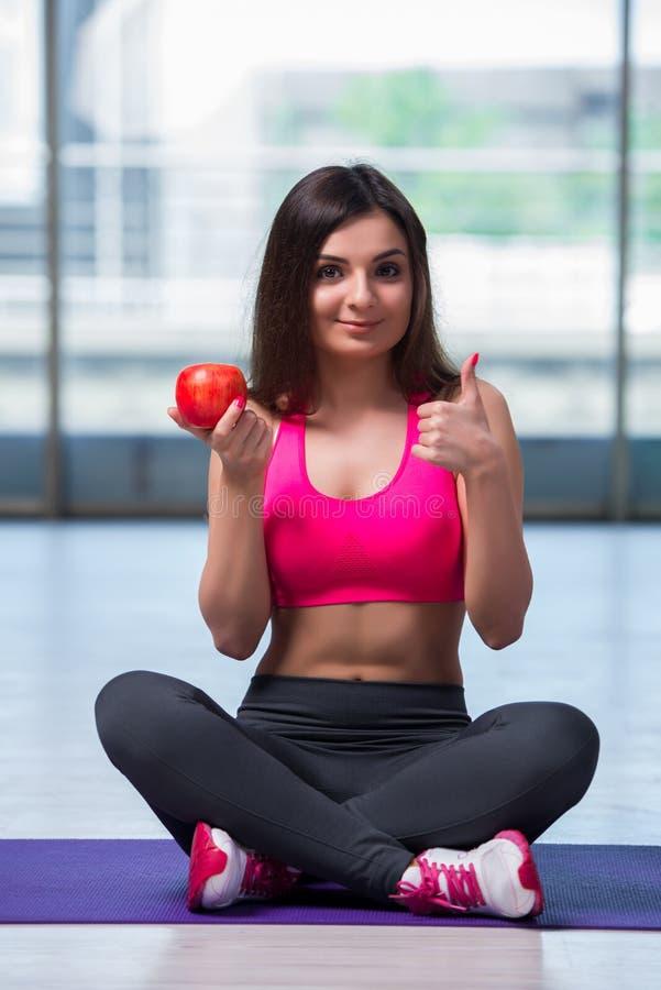 A jovem mulher que come a maçã vermelha no conceito da saúde fotografia de stock