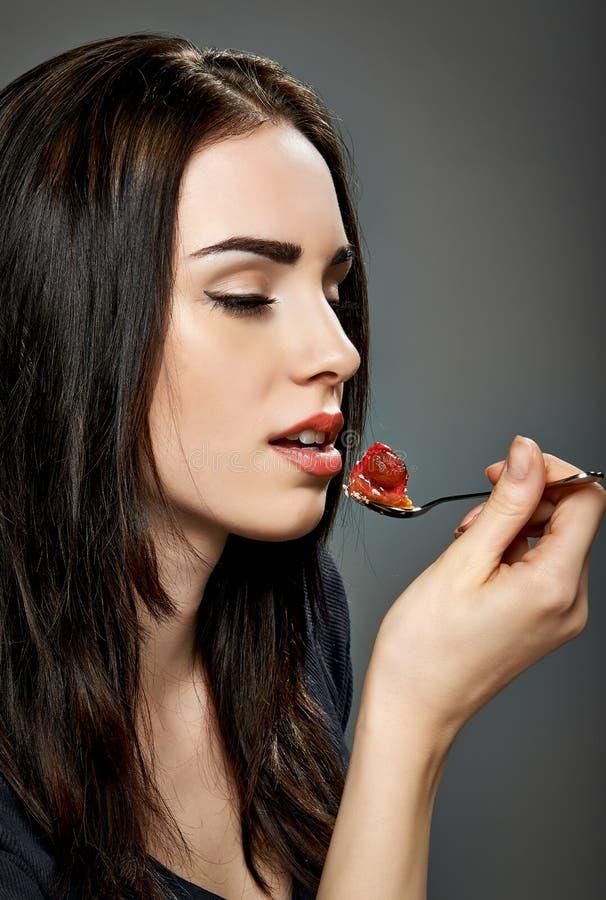 Jovem mulher que come o bolo da morango imagens de stock