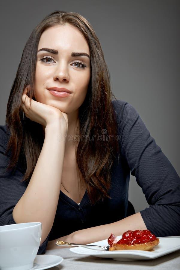 Jovem mulher que come o bolo da morango fotos de stock royalty free