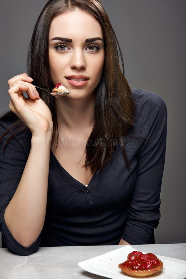 Jovem mulher que come o bolo da morango fotografia de stock