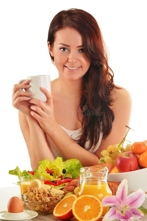 Jovem mulher que come o café da manhã fotos de stock royalty free