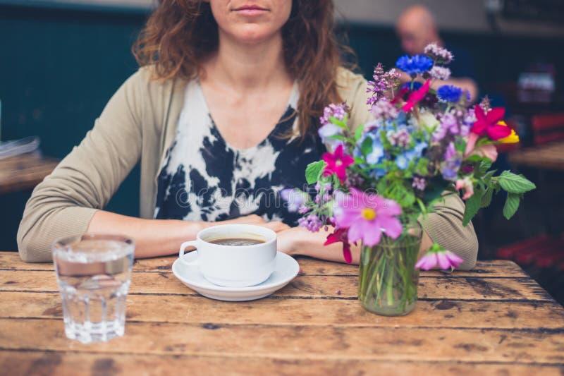 Jovem mulher que come o café no café foto de stock