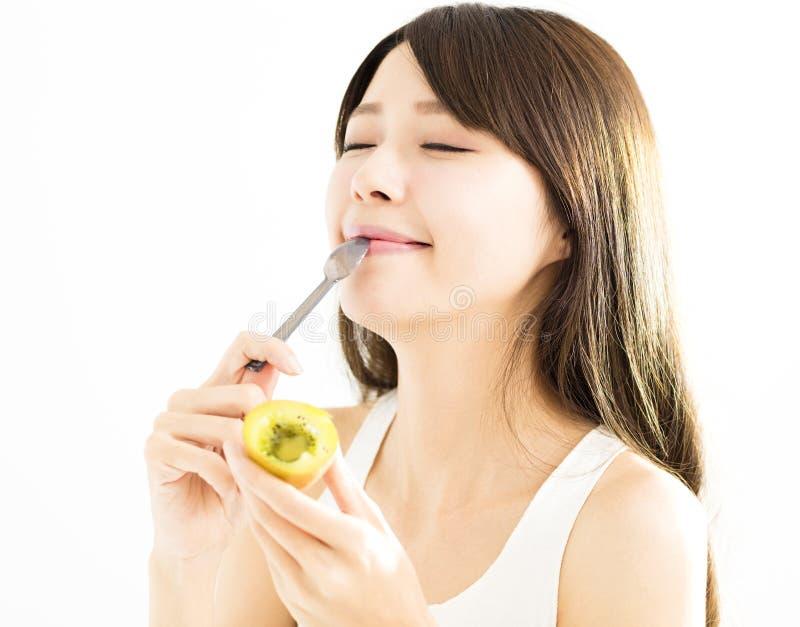 Jovem mulher que come o fruto de quivi imagens de stock royalty free