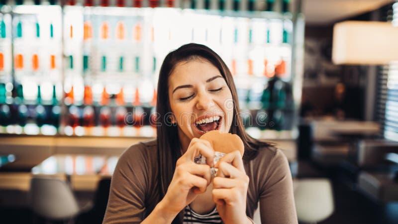 Jovem mulher que come o Hamburger gordo Fast food da ânsia Apreciando o prazer culpado, comendo a comida lixo Expressão satisfeit fotografia de stock royalty free