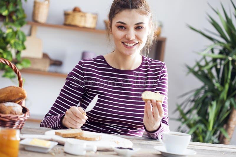 Jovem mulher que come o pão com manteiga fotos de stock royalty free