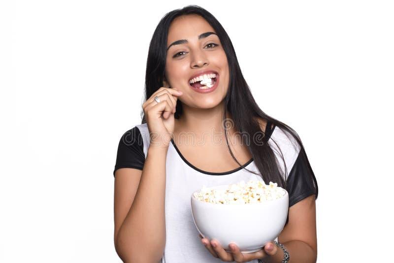 Jovem mulher que come a pipoca fotografia de stock
