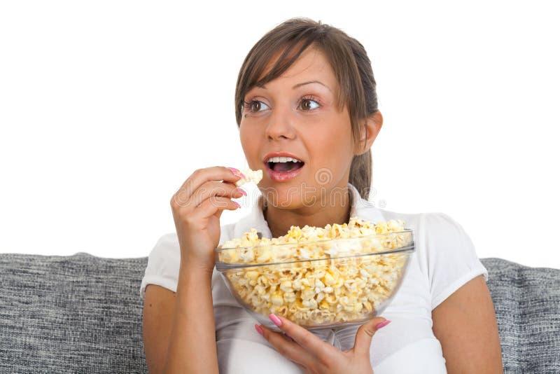 Jovem mulher que come a pipoca foto de stock
