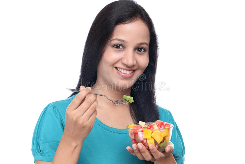 Jovem mulher que come a salada de fruto imagem de stock royalty free