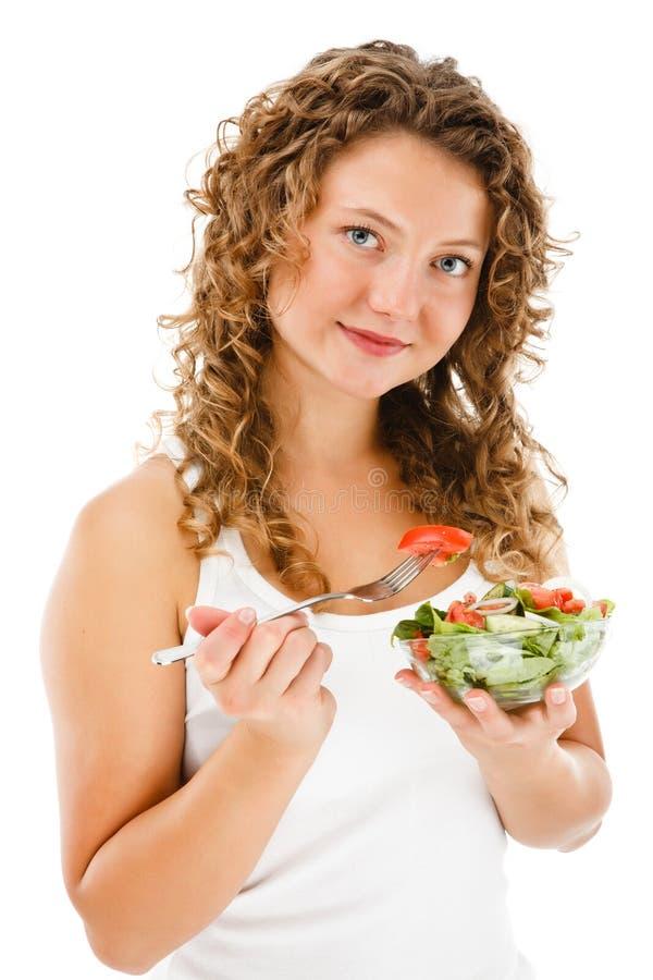 Jovem mulher que come a salada vegetal no fundo branco fotografia de stock royalty free