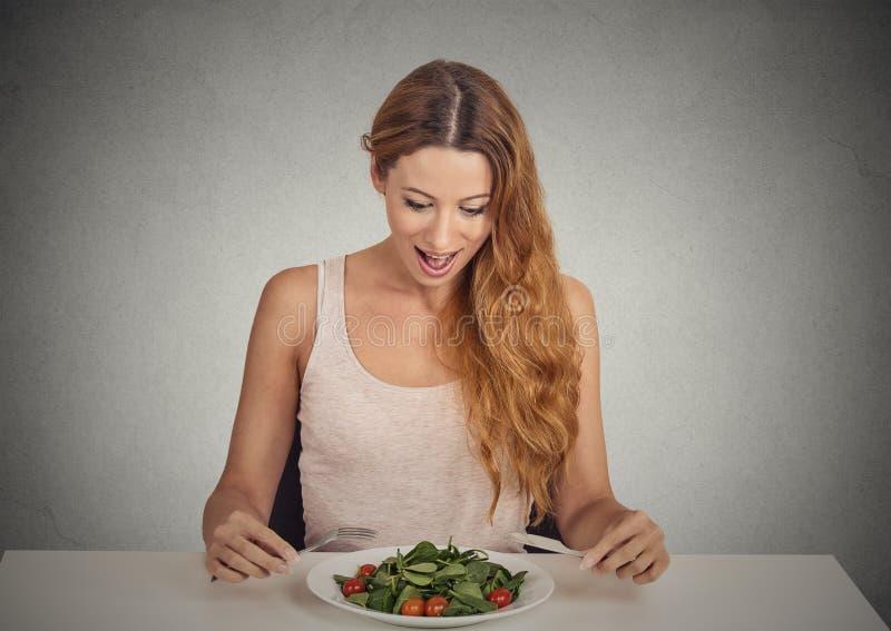 Jovem mulher que come a salada verde imagens de stock royalty free
