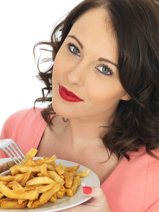 Jovem mulher que come a salsicha e microplaquetas enormes fotografia de stock