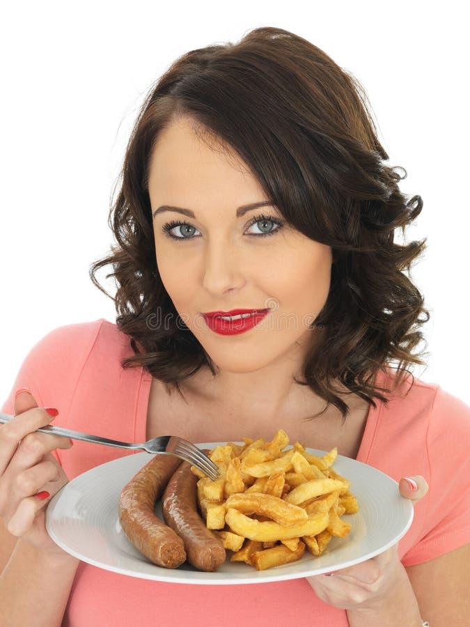 Jovem mulher que come a salsicha e microplaquetas enormes imagens de stock royalty free