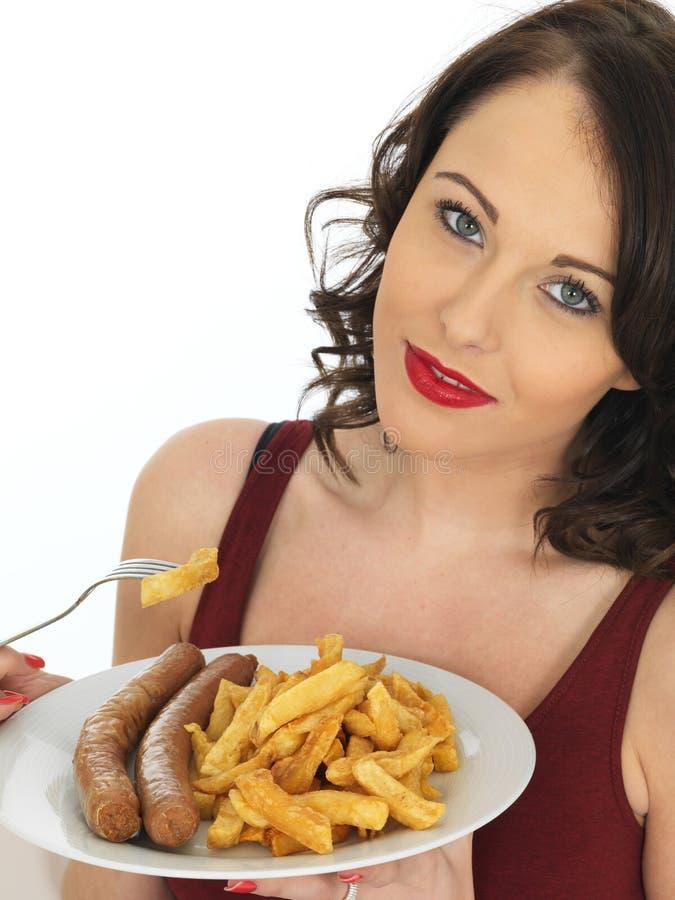Jovem mulher que come a salsicha e microplaquetas enormes fotografia de stock royalty free