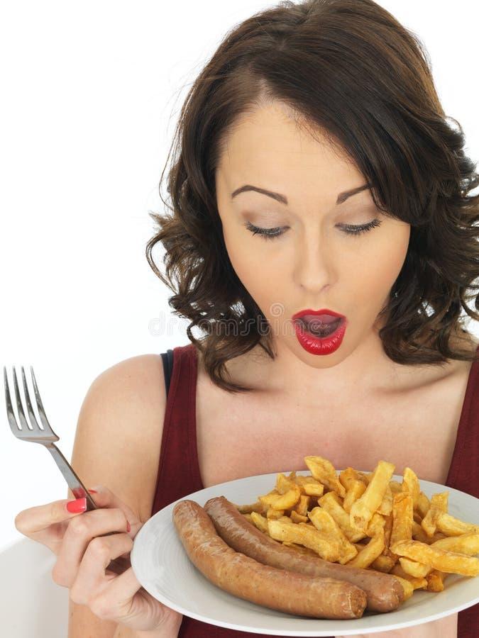 Jovem mulher que come a salsicha e microplaquetas enormes fotos de stock
