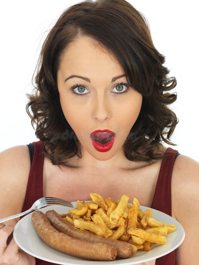 Jovem mulher que come a salsicha e microplaquetas enormes fotos de stock royalty free