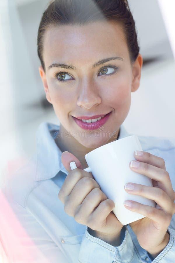 Jovem mulher que come um café na cozinha