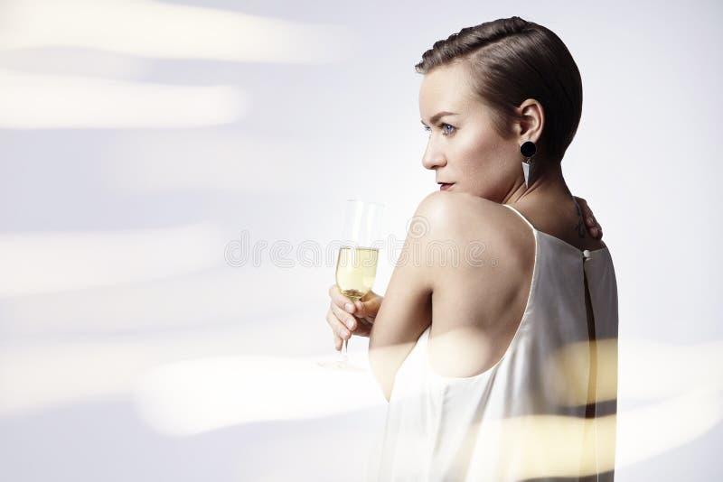 Jovem mulher que comemora com champanhe Alargamentos no fundo Partido, ano novo, conceito do Natal fotografia de stock royalty free