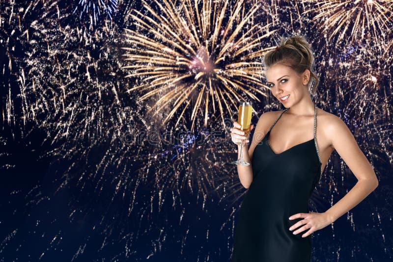 Jovem mulher que comemora com champanhe em suas mãos foto de stock