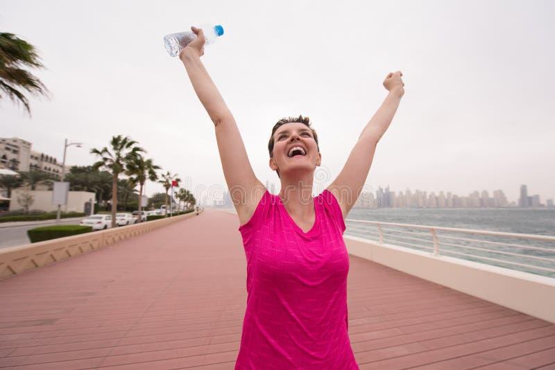 Jovem mulher que comemora uma corrida bem sucedida do treinamento foto de stock
