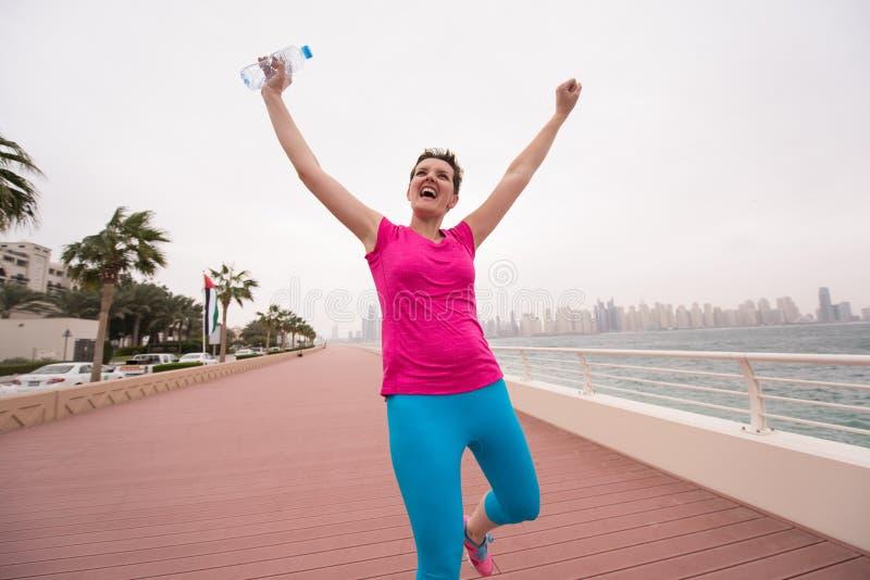 Jovem mulher que comemora uma corrida bem sucedida do treinamento fotografia de stock royalty free
