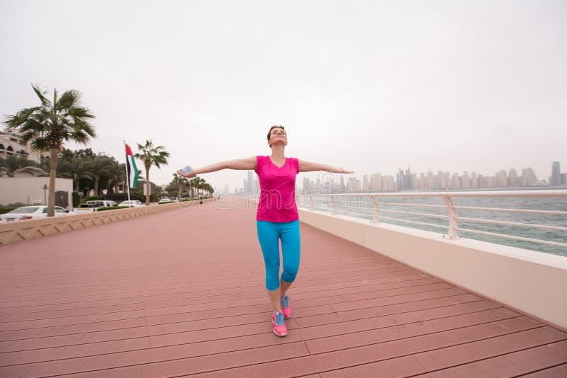 Jovem mulher que comemora uma corrida bem sucedida do treinamento fotos de stock