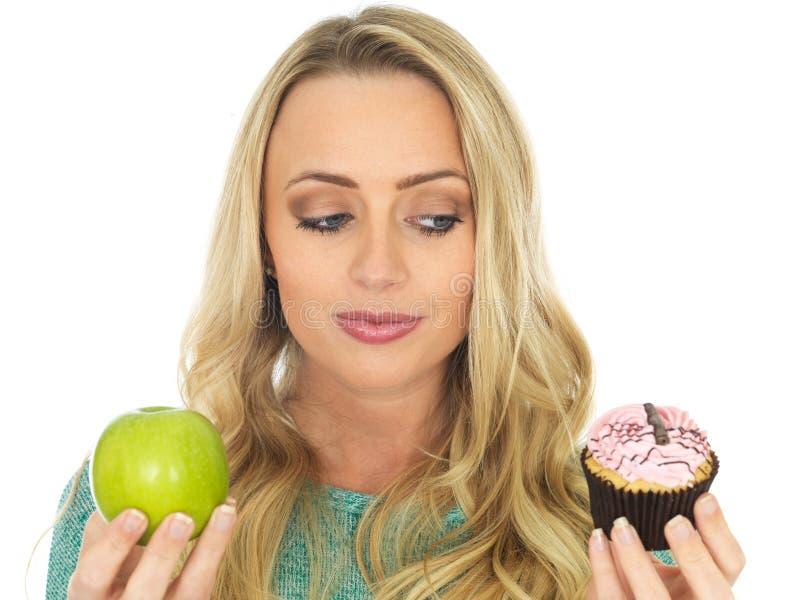 Jovem mulher que compara o bom e alimento mau imagem de stock royalty free