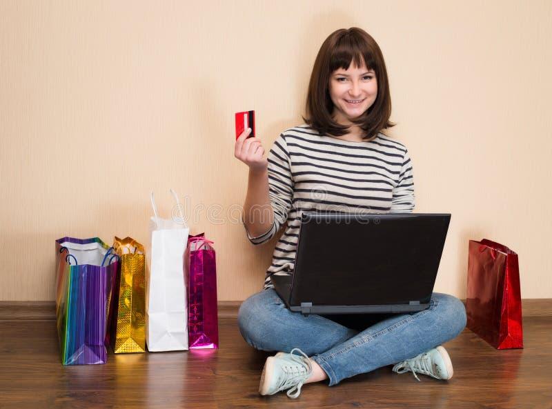 jovem mulher que compra em linha em casa A menina com sacos de compras senta-se imagens de stock