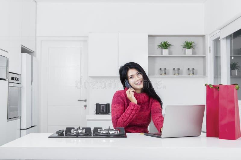 Jovem mulher que compra em linha na cozinha imagens de stock