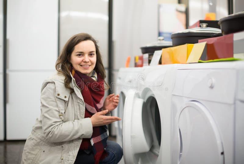 Jovem mulher que compra a máquina nova da lavanderia no supermercado foto de stock royalty free