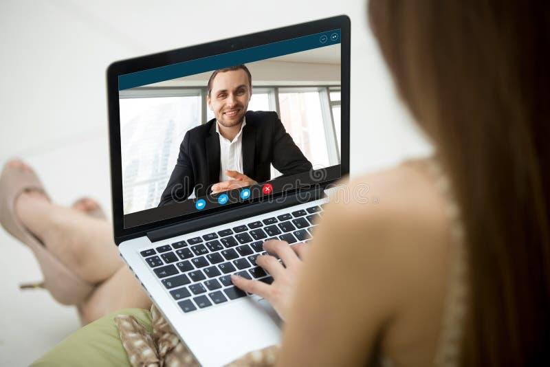 Jovem mulher que comunica-se com o homem através da aplicação video da chamada foto de stock