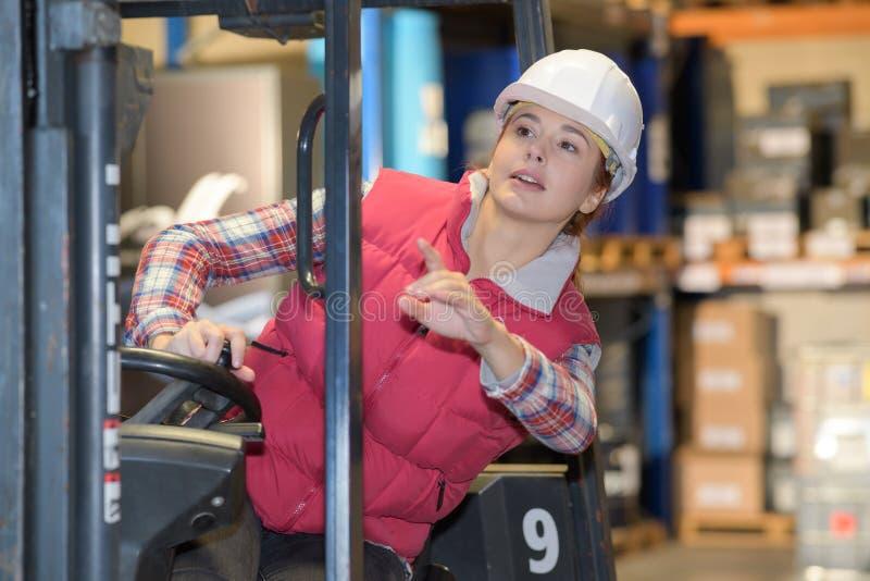 Jovem mulher que conduz o caminhão do alcance no armazém imagem de stock
