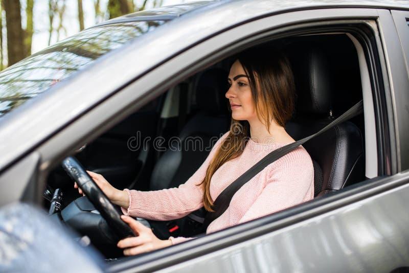Jovem mulher que conduz seu carro com a correia do safity na estrada da rua Movimentação segura imagens de stock royalty free