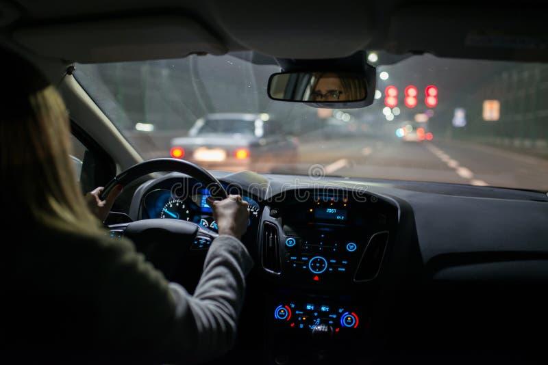 Jovem mulher que conduz um carro na noite imagens de stock royalty free