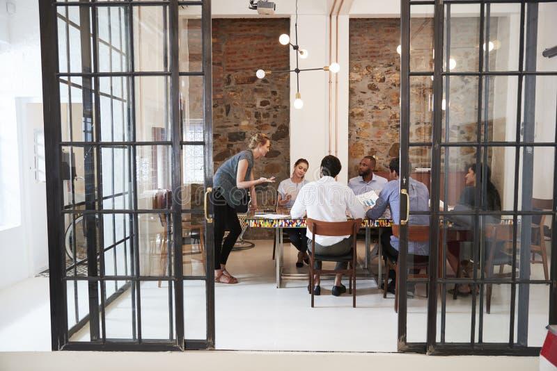 Jovem mulher que controla uma reunião da equipe em uma sala de reuniões imagens de stock