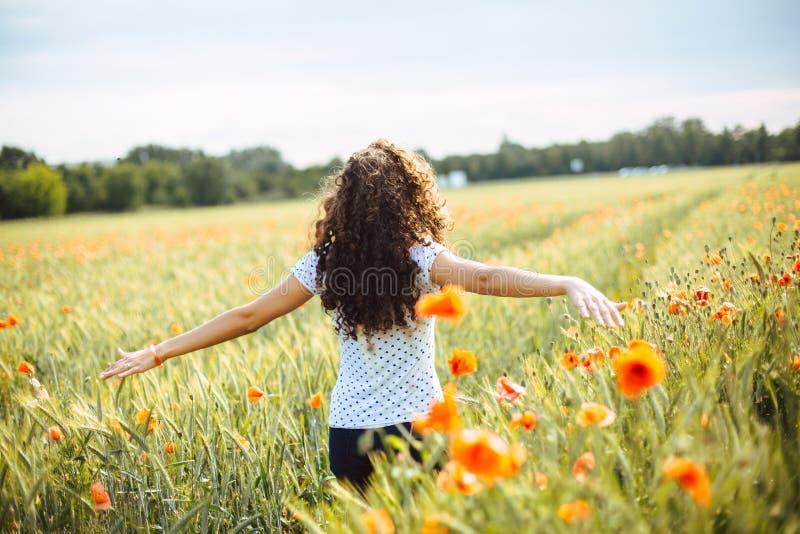 Jovem mulher que corre através de um campo dos wildflowers imagem de stock royalty free