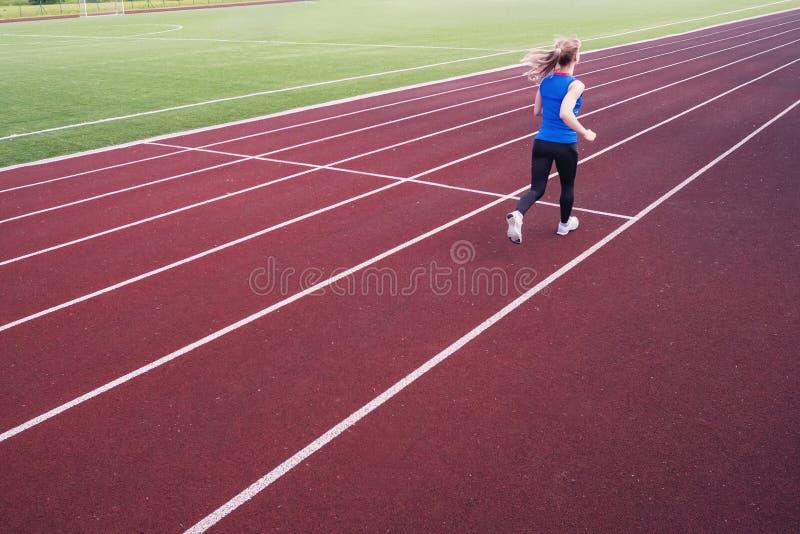 Jovem mulher que corre durante a noite ensolarada na trilha do estádio Um louro em um t-shirt azul e em umas caneleiras pretas co fotos de stock royalty free