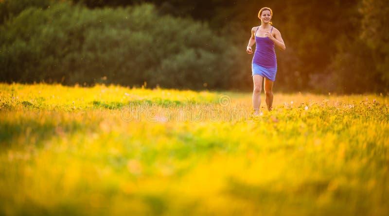 Jovem mulher que corre fora em evenis ensolarados bonitos de um verão fotografia de stock