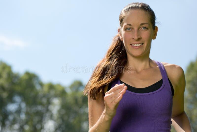 Jovem mulher que corre fora a formação para a corrida da maratona imagens de stock royalty free