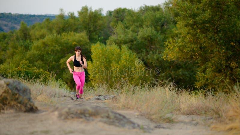 Jovem mulher que corre na fuga de montanha da manhã Conceito ativo do estilo de vida fotografia de stock